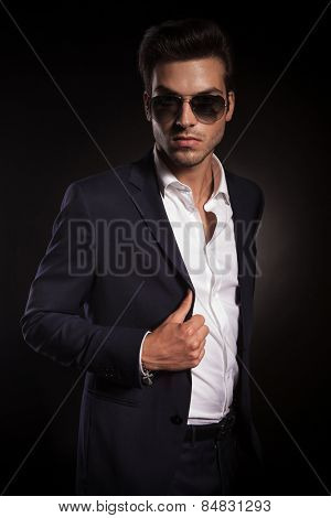 Portrait of a elegant business man posing on black studio background, fixing his jacket while looking at the camera.