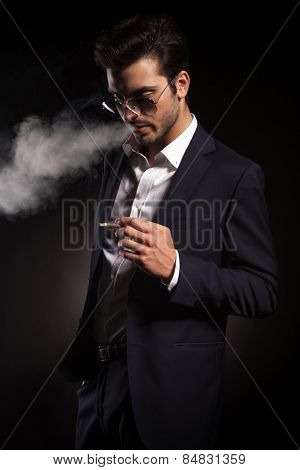 Handsome young business man holding a cigarette in his hand while blowing smoke.
