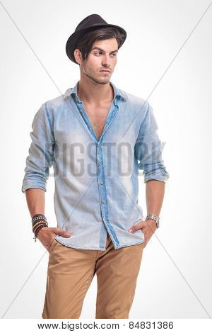 Young fashion man looking away from the camera while holding both hands in his pocket.