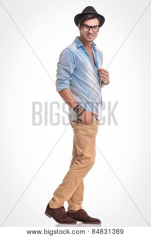 Full body image of a fashion man looking at the camera while holding one hand in his pocket.