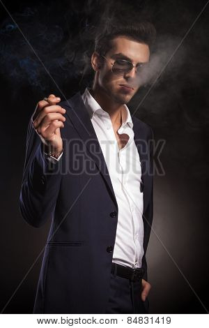 Side view of a young elegant business man holding one hand in his pocket while smoking a cigarette.