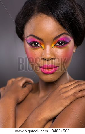 beautiful african female model with colorful makeup on black background