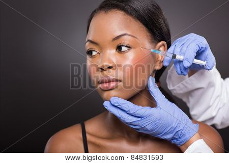 beautiful afro american woman receiving plastic surgery injection on her face