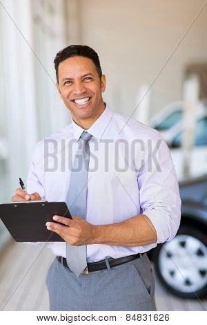 handsome car dealership salesman working in showroom