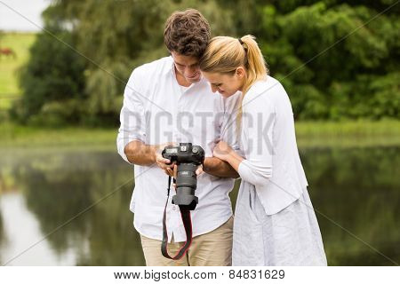 happy young couple viewing pictures on camera outdoors