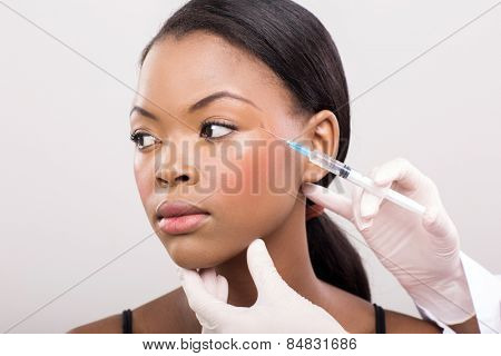cosmetic doctor injecting african woman face close up