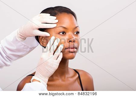 dermatologist checking young african american woman face skin on plain background