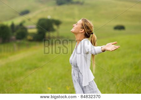 pretty woman with arms outstretched in countryside