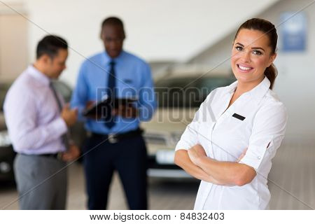attractive female vehicle sales consultant standing in showroom