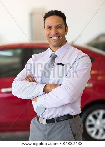 happy male car dealer principal inside showroom