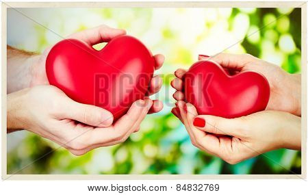 Loving couple holding hearts in hands on sunny nature background