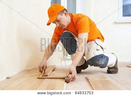carpenter worker measuring wood parquet board during flooring work with hammer