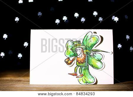 Greeting card for Saint Patrick's Day with Leprechaun on wooden table on dark lights background