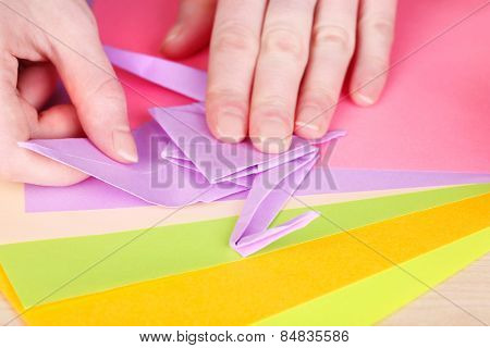 Hands making origami crane, close up