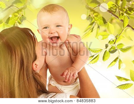 Cute baby boy and his mother on natural background