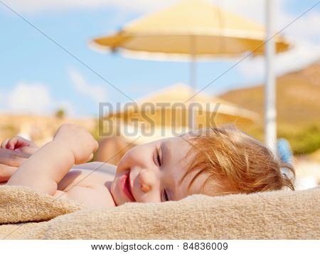 Happy Baby Sunbathing On The Beach Sunbed
