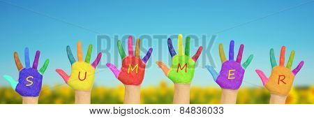 Kid's Painted Hands Against Blue Sky