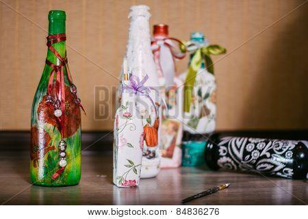Decoupage bottles lying on the floor .