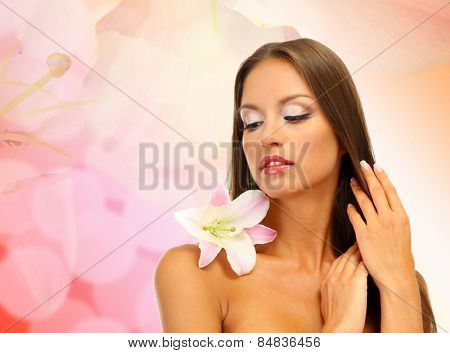 Beautiful young woman with lily flower on bright pink background