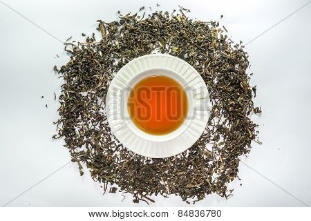 A white cup of tea in the center of dried tea leaf