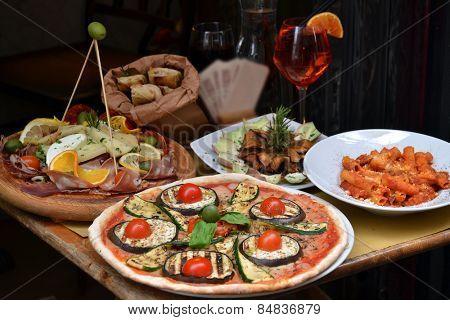 Pizza and food arrangement outside an italian restaurant.