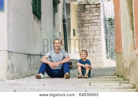 Father And Little Son Siting On The Old Croatian Town Street