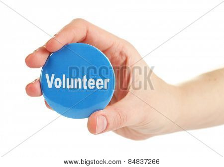 Round volunteer button in hand isolated on white