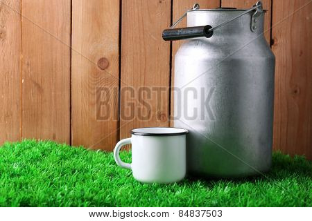 Retro can for milk and mug with milk  on green grass, on wooden background