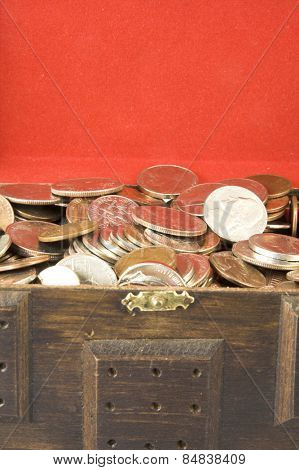 Money in a wooden chest with red background