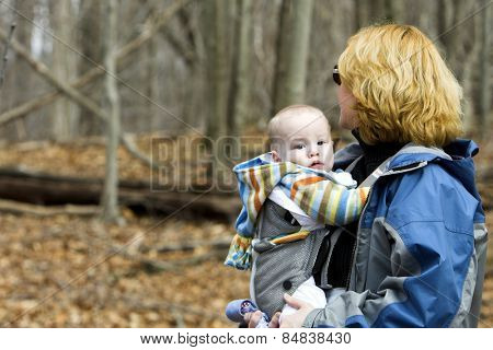 Baby being carried by mother in woods