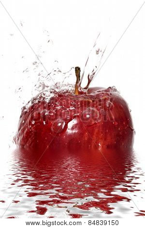 Water splashing down on an apple with reflection
