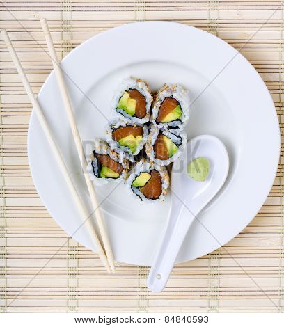 Raw fish and avocado sushi on a white plate with chopsticks and wasabi