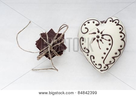 Ginger white heart shaped cookie as a present with pile of dark chocolate on white background