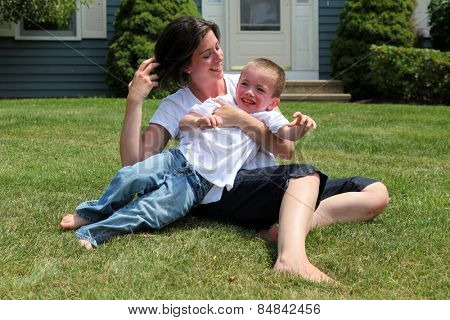 Pretty mother and son playing on grass