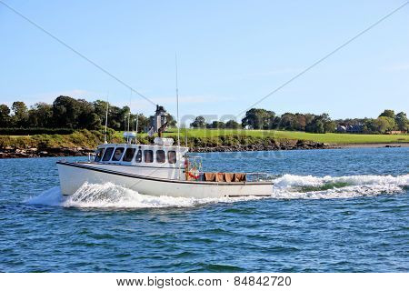 Fishing boat moving past beautiful coastline