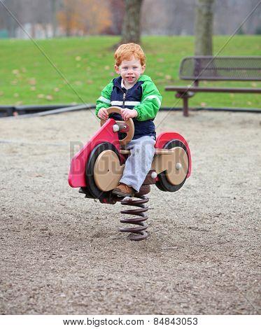 Boy on spring toy in kids playground