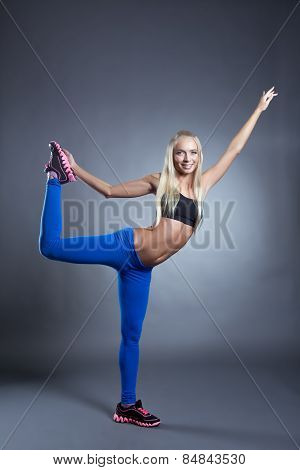 Pretty pilates instructor posing in studio