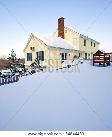 Typical colonial style house in deep snow and ice