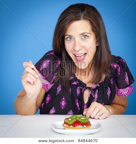 Attractive woman with a fruit tart in studio