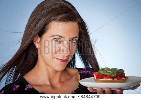 Attractive woman with two desserts in studio