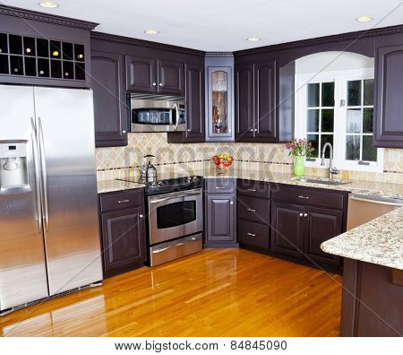 Modern domestic kitchen with new appliances and wooden floor