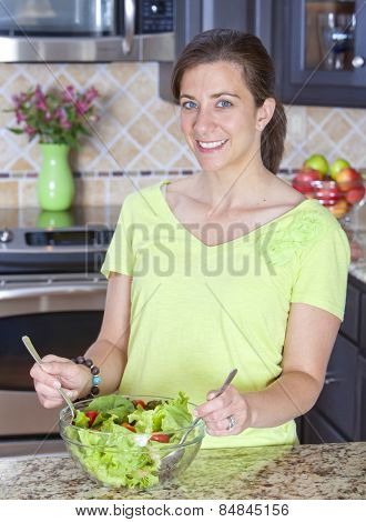 Pretty woman mixing salad in a glass bowl