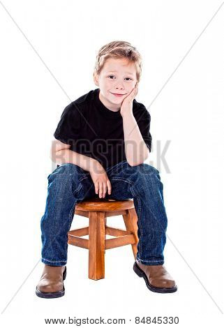 Cute boy in studio sitting on a stool