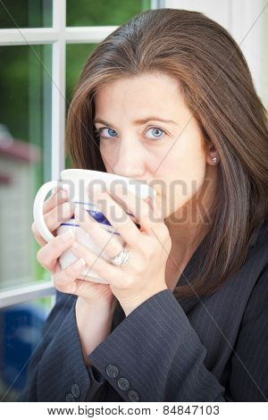 Pretty adult woman sipping drink with sad expression