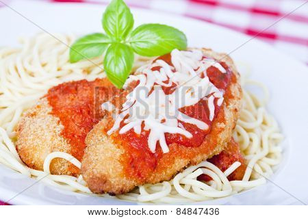 Chicken parmigiana on a white plate with spaghetti