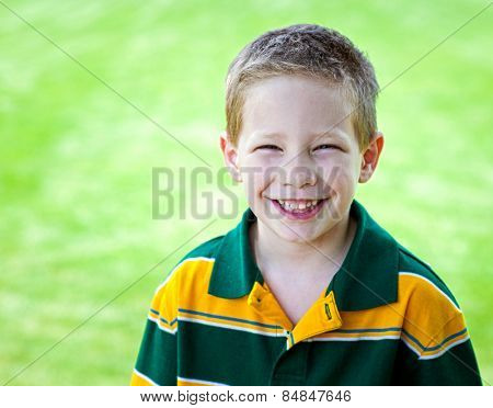 Cute boy with big smile outdoors portrait