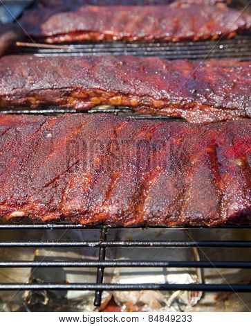 Racks of BBQ ribs on a hot grill
