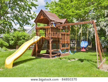 Back Yard Wooden Swing Set on Green Lawn