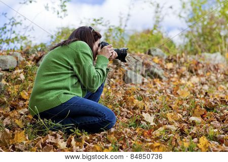 Female photographer crouching in fall leaves to take a picture