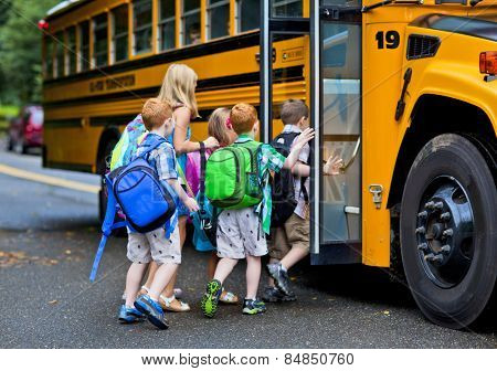 A group of young children getting on the schoolbus